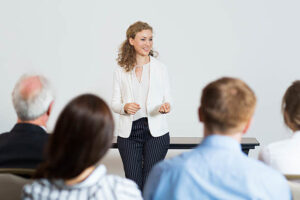 successful-young-businesswoman-speaking-in-front-of-audience-at-picture